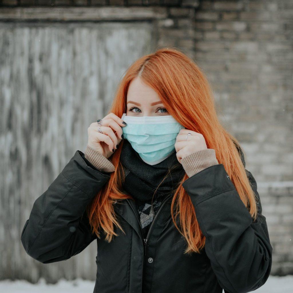 دختر مسافر با ماسکی بر دهان نشان از بحران صنعت گردشگری در دوران ویروس کرونا دارد